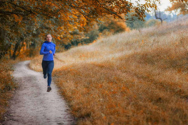 young slim athleic jogger woman runs along the path  on the  beautiful  autumnal forest. - carpet runner stock photos and pictures