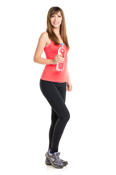 Young slim caucasian woman holding a bottle of fresh water Young slim caucasian woman holding a bottle of fresh water. Smiling fitness girl isolated on white background sergionicr stock pictures, royalty-free photos & images
