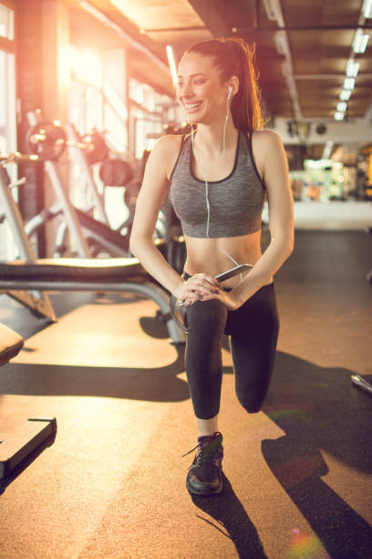 Young slim fit woman doing lunges in gym stock photo