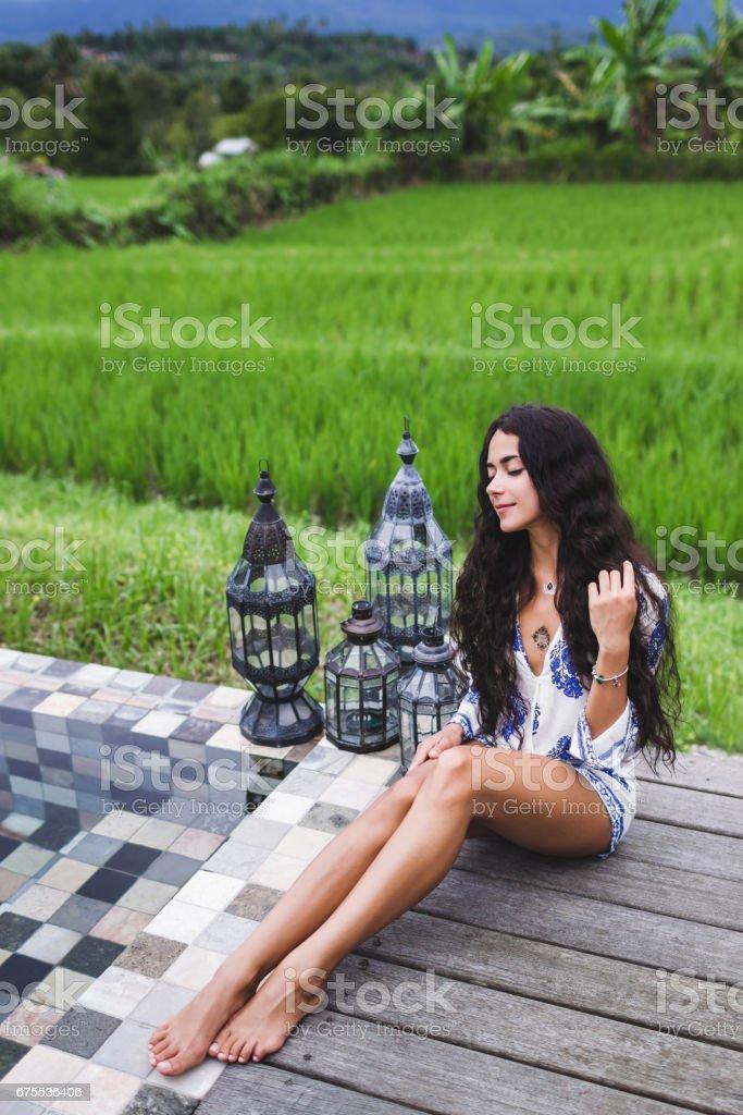 Jeune fille mince reposante près de la piscine de luxe dans les rizières de Bali photo libre de droits