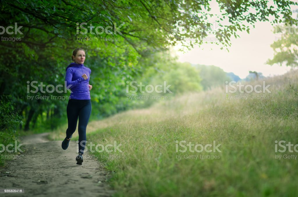 young slim runner  in a black sports leggins and and blue jacket  fast runs along the path  on the  beautiful green forest. stock photo