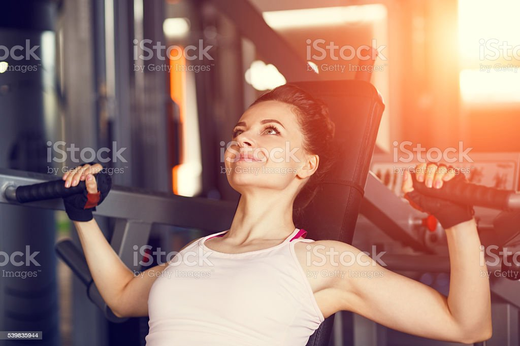 Young slim woman doing chest fly exercise in gym stock photo
