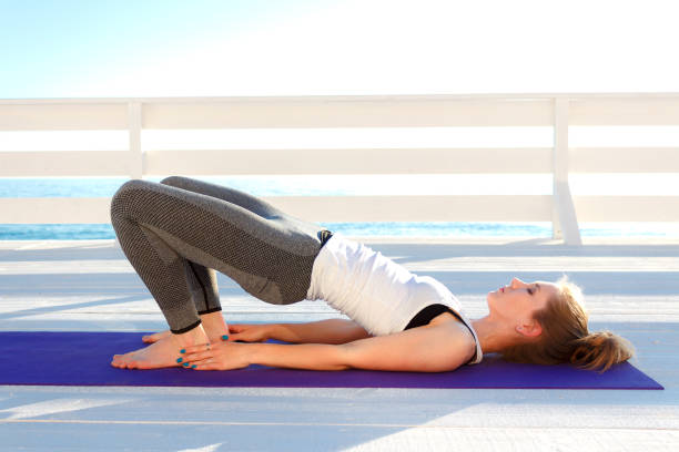 Young slim woman in tight sportswear practicing yoga outdoors at white wooden seafront. Pelvic lift exercise stock photo