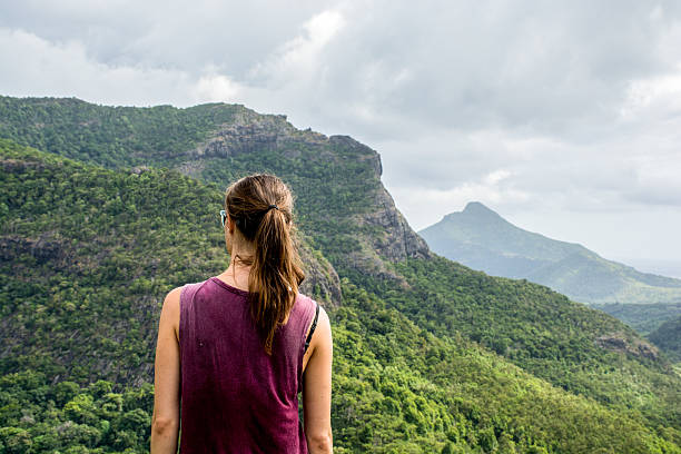 Young slim woman looking over the mountains stock photo