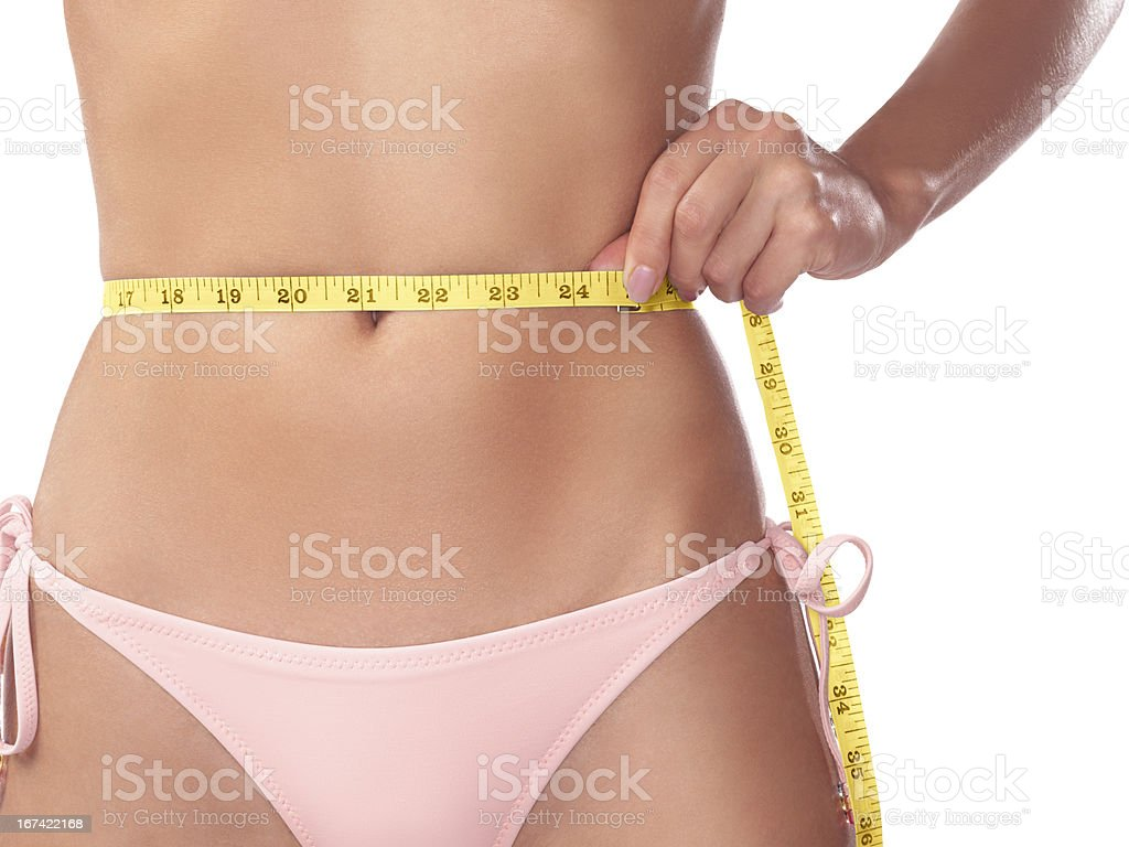 Young slim woman measuring her waist with a tape royalty-free stock photo