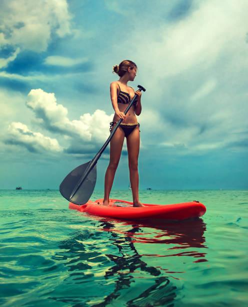 junge schlanke frau auf die paddleboard. aktiven lebensstil und wasser sport. - stehpaddeln stock-fotos und bilder
