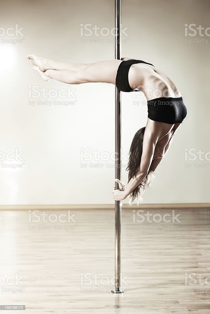 A young, slim woman pole dancing stock photo
