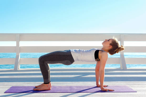 Young slim woman practicing yoga in table pose outdoors at white wooden seafront stock photo