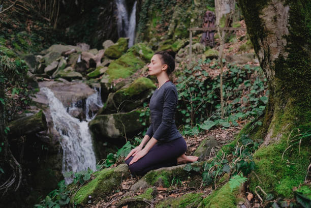 Young slim woman practicing yoga outdoors in moss forest on background of waterfall. Unity with nature concept. Girl meditates sitting stock photo