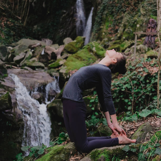 Young slim woman practicing yoga outdoors in moss forest on background of waterfall. Unity with nature concept. Girl in camel position stock photo