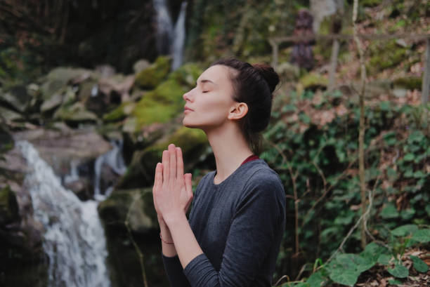 Young slim woman practicing yoga outdoors in moss forest on background of waterfall. Unity with nature concept. Girl standing with prayer hands stock photo