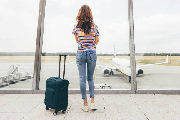 young slim woman waiting her flight in lounge hall (just after duty free) in airport with her hand luggage (green trolley). lost or canceled flight, need compensation concept. eindhoven, netherlands - donna valigia solitudine foto e immagini stock