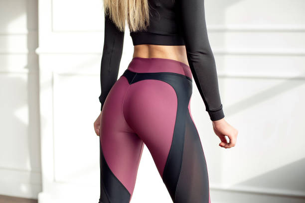 ung smal kvinna med en atletisk kropp långt blont hår klädd i svart sport sportkläder topp och leggings som står i ljusa yoga rum med stora panoramafönster förbereder innan utbildning hälso-liv - bum bildbanksfoton och bilder