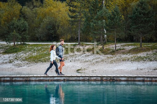 Side view of couple in 20s and 30s walking on Jasna Lake pier in alpine town of Kranjska Gora in northwestern Slovenia.