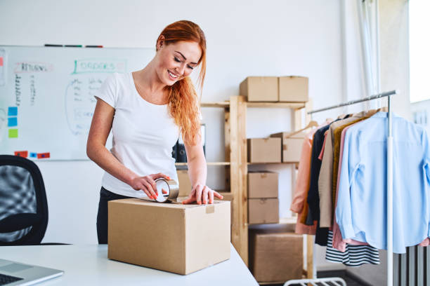 Young small business owner packing deliveries in modern office and storage space stock photo