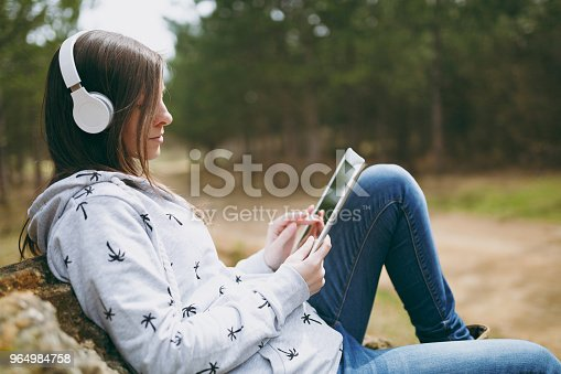 862602714istockphoto Young smart beautiful woman in casual clothes with headphones sitting on stone using tablet pc computer in city park or forest on green blurred background. Student lifestyle, leisure concept. 964984758