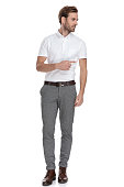 istock young smart casual man pointing finger to side 1131989180