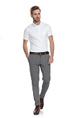 istock young smart casual man walking with hand in pocket 1131989413