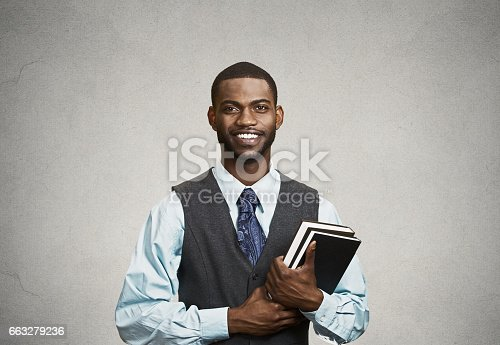 Closeup young smart, happy, smiling handsome man holding books, prepared, ready to ace his exam test finals, isolated black, grey background. Positive human facial expression feeling, emotion attitude