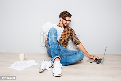 947303582 istock photo Young smart man with cup of coffee typing on laptop 944992788