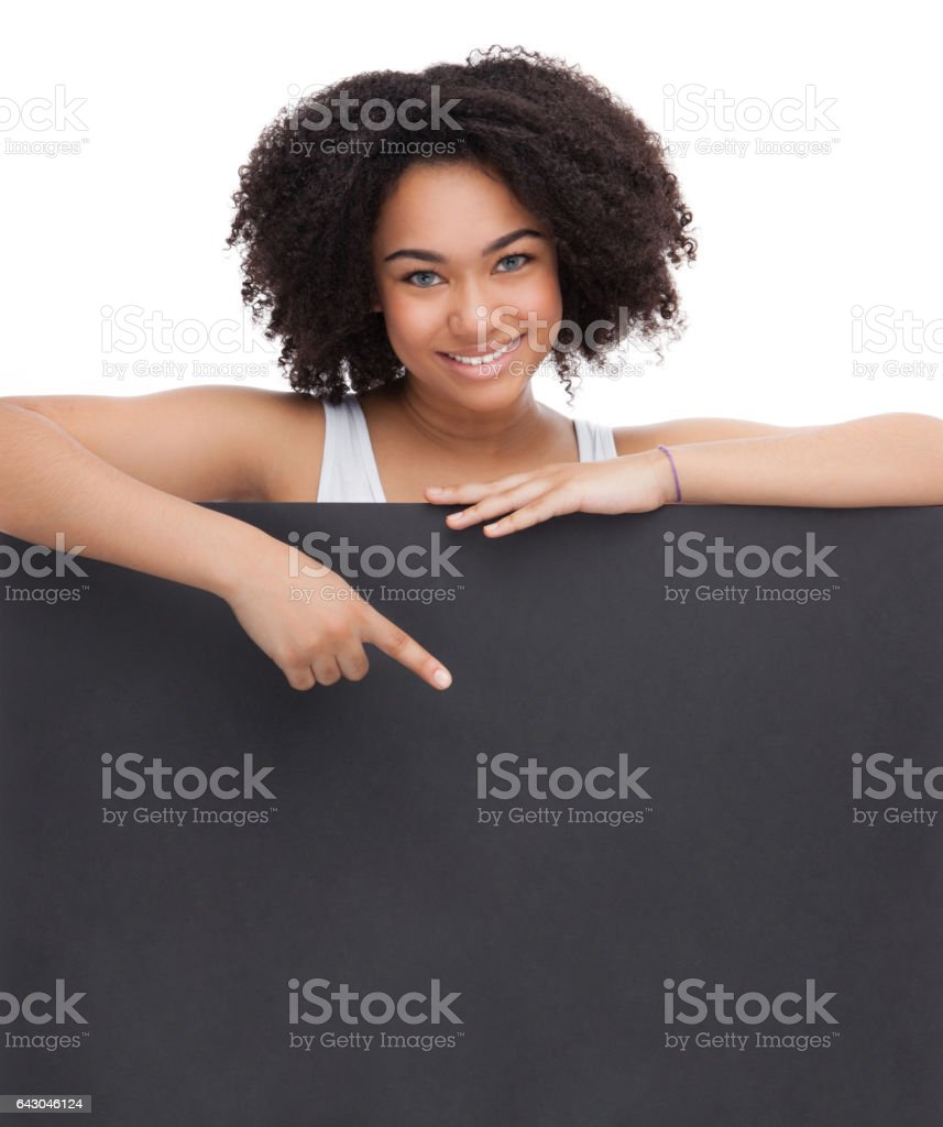 Young Smileing teenager african girl hold black blank paper and shows on it. stock photo