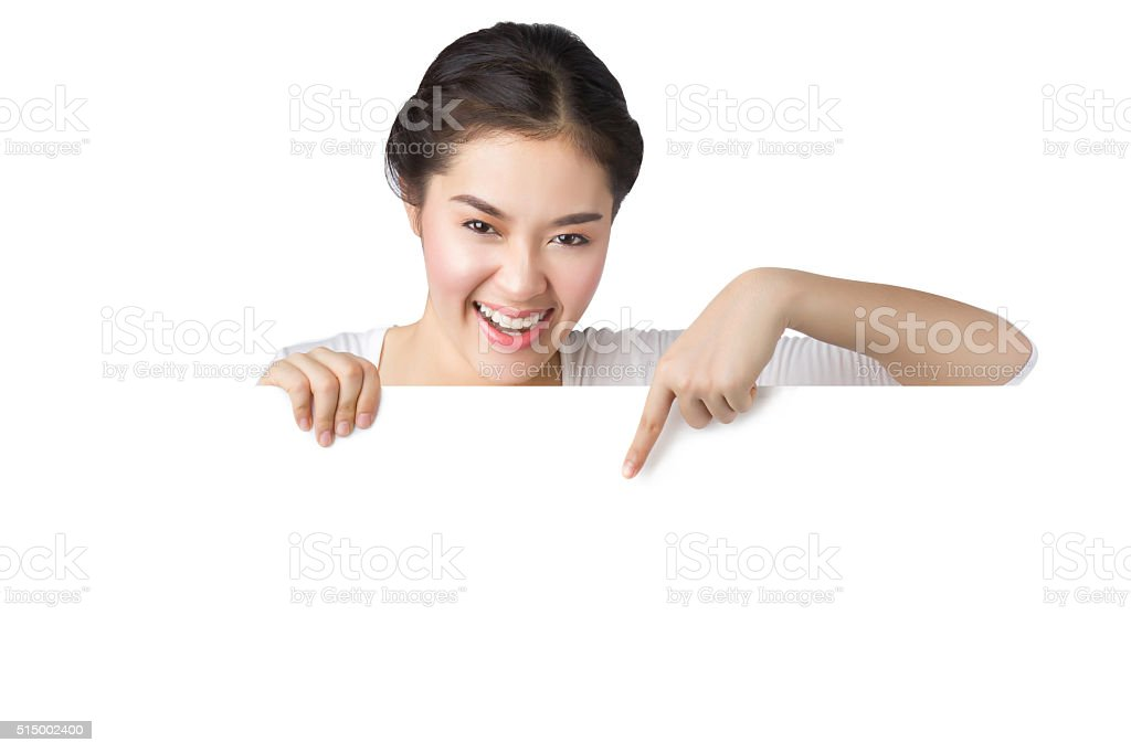 Young smiley Asian woman showing and pointing at blank billboard