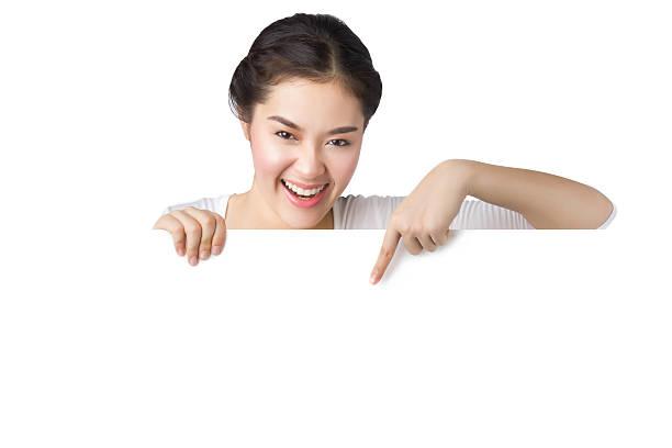 Sonriente joven asiático mujer mostrando y señalando en blanco cartelera - foto de stock