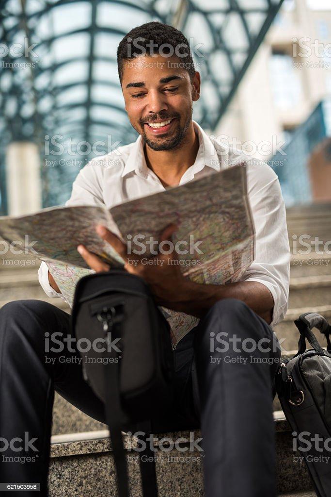 Junge lächelnd afroamerikanischer Geschäftsmann schaut an Kartographie. Lizenzfreies stock-foto