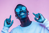 istock Young smiling african american man listening to music with earphones, dancing isolated on pink background 1090819338