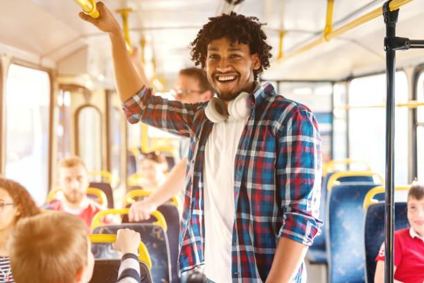 jonge glimlachend african american man rijden in de stadsbus en camera te kijken. - forens stockfoto's en -beelden