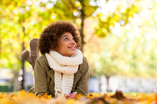 Young smiling African American woman lying on fall leaves