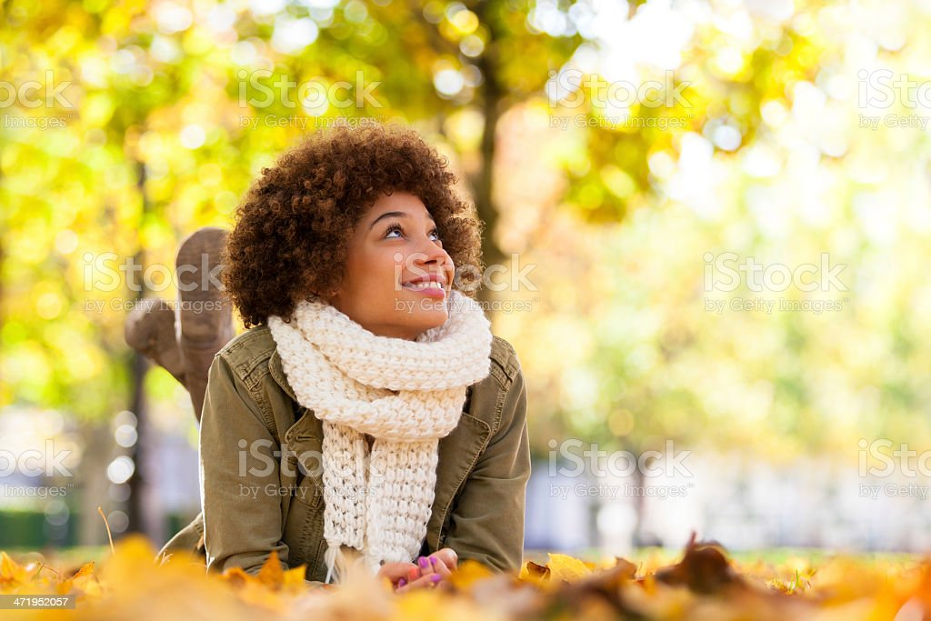 Young smiling African American woman lying on fall leaves stock photo