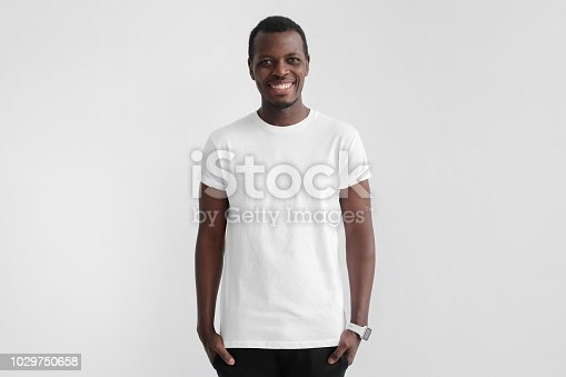 1018069806 istock photo Young smiling african man with dark skin standing with hands in pockets, wearing blank white t shirt with copy space for your logo or text, isolated on gray background 1029750658