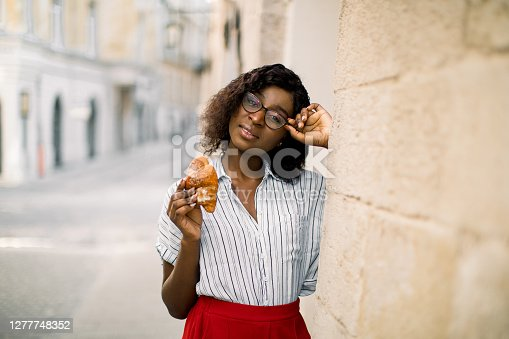 Young smiling afro-american girl in eyeglasses, holding tasty croissant, while posing to camera with smile, standing near olf city building outdoor. Summer holidays, lunch time and vacation concept