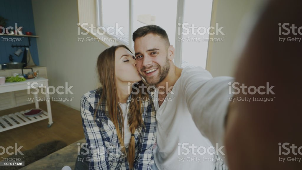 POV of Young smiling and beautiful couple take selfie portrait on smartphone camera and kiss while sitting on bed in the morning stock photo