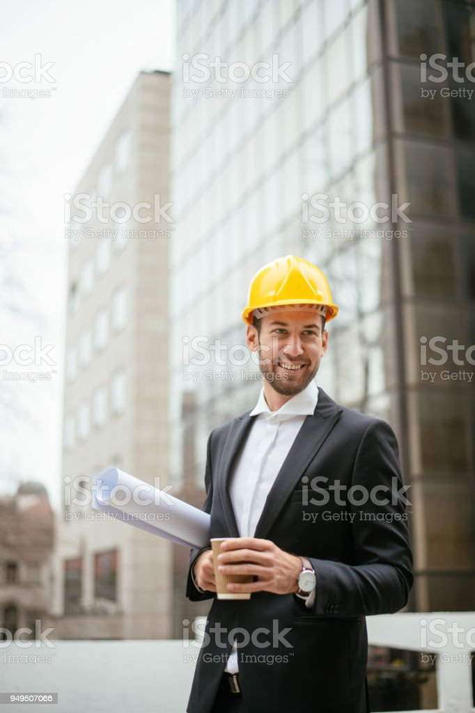 Young smiling architect holding blueprint and drinking coffee....