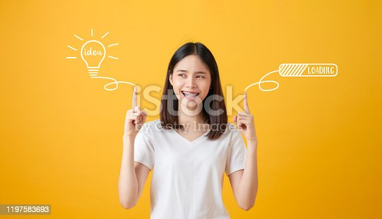 1162297213 istock photo Young smiling Asian woman pointing hands to light bulb with text ideas and loading brainstorm on yellow background. 1197583693