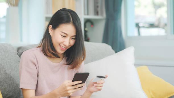 Junge lächelnde asiatische Frau mit Smartphone kaufen Online-Shopping per Kreditkarte, während auf dem Sofa liegen, wenn im Wohnzimmer zu Hause entspannen. Lifestyle Latin und hispanische ethnostizität Frauen im Haus Konzept. – Foto