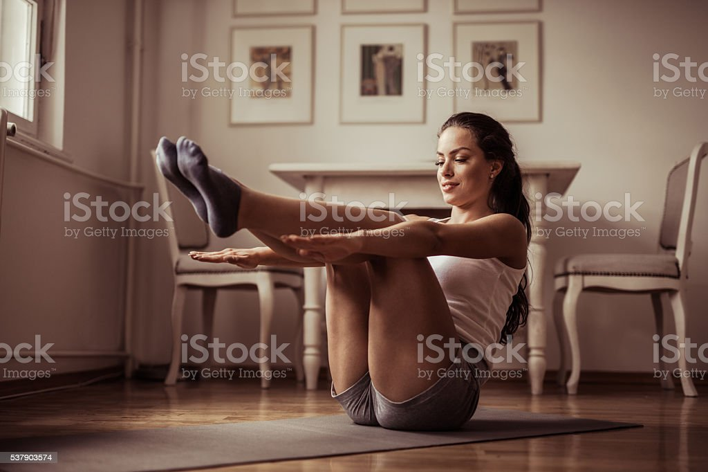 Young smiling athletic woman doing sit-ups at home. stock photo
