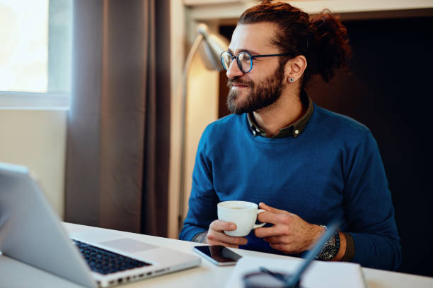 Young smiling attractive freelancer sitting in his office and taking coffee break from work. stock photo