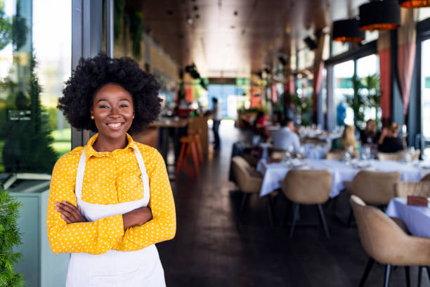 young smiling barista wearing apron, standing - small business owner stock pictures, royalty-free photos & images