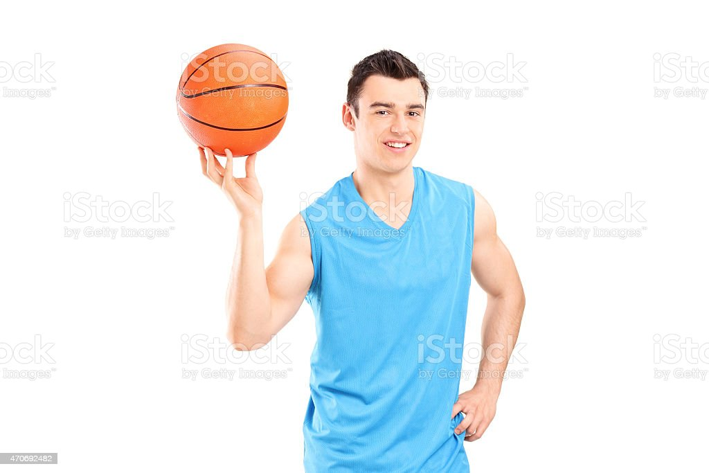 Young smiling basketball player in blue dress posing with a ball...