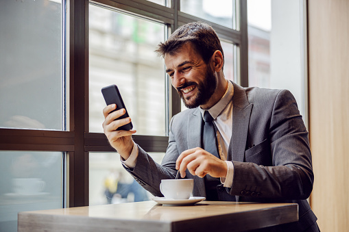 Young smiling bearded businessman sitting in coffee shop, reading something funny on smart phone and stirring coffee.