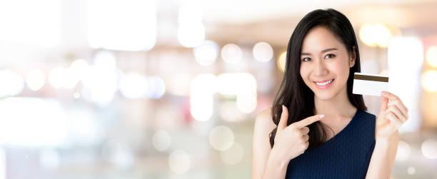 jonge lachende mooie aziatische vrouw presenteren creditcard in de hand - portait background stockfoto's en -beelden