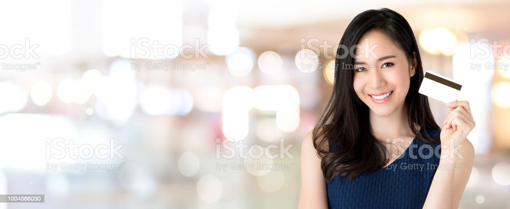 Young smiling beautiful Asian woman presenting credit card in hand,...
