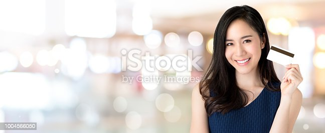 istock Young smiling beautiful Asian woman presenting credit card in hand 1004566050