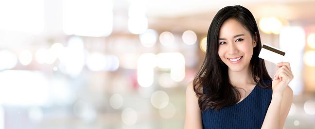 Jonge Lachende Mooie Aziatische Vrouw Presenteren Creditcard In De Hand Stockfoto en meer beelden van Achtergrond - Thema
