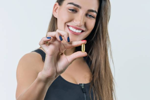 Joven sonriente a mujer saludable hermosa en ropa deportiva con vitamina D, E, un aceite de pescado omega-3 cápsulas, sobre fondo blanco - foto de stock