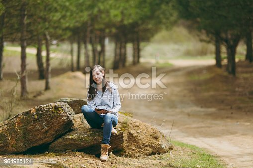 862602714istockphoto Young smiling beautiful woman in casual clothes sitting on stone cross-legged using tablet pc computer in park or forest on green blurred background. Student education. Lifestyle, leisure concept. 964985124