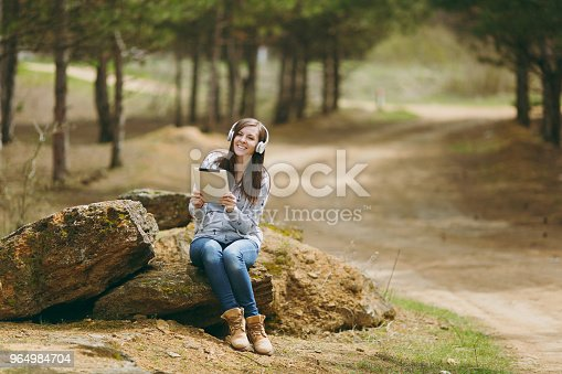862602714istockphoto Young smiling beautiful woman in casual clothes with headphones sitting on stone using tablet pc computer in city park or forest on green blurred background. Student lifestyle, leisure concept. 964984704